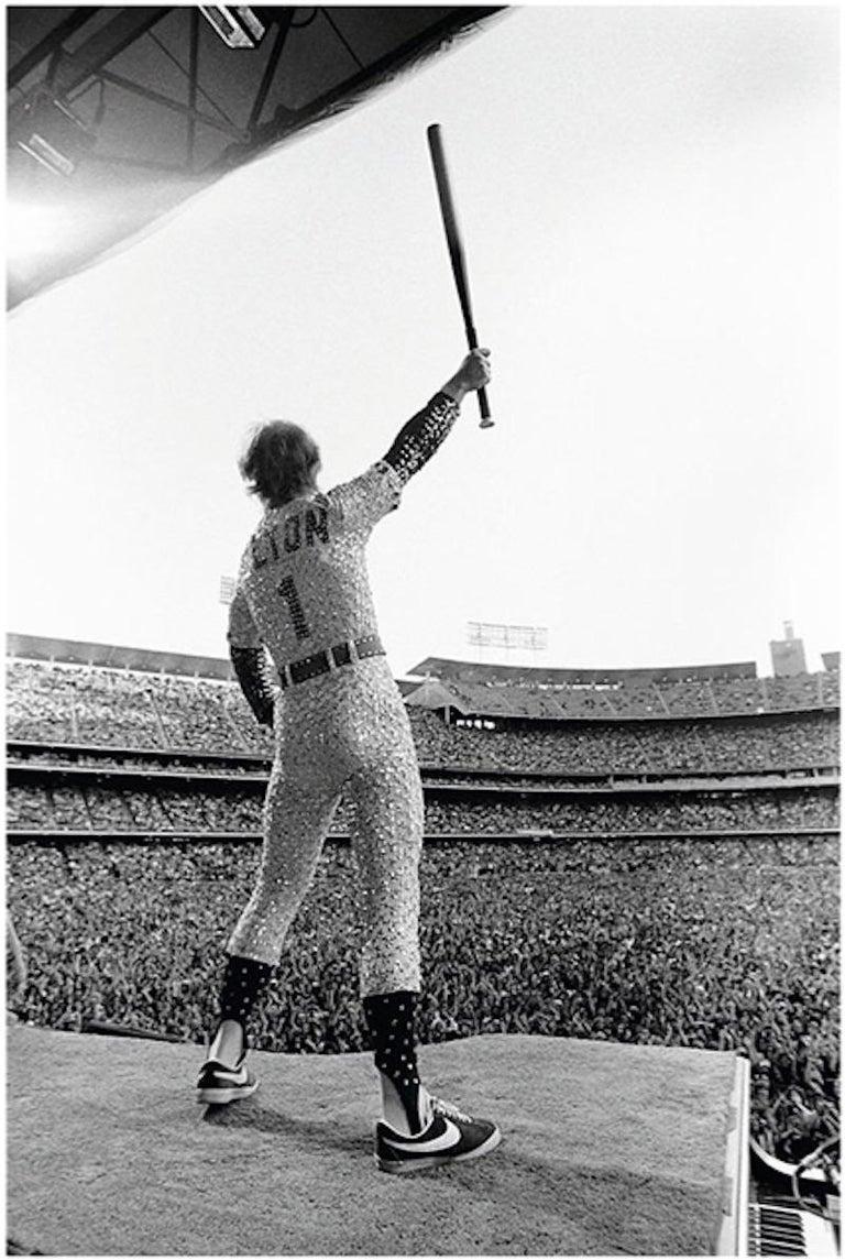 Terry O'Neill Portrait Photograph - Elton John, Saluting, Dodger Stadium, Los Angeles, October 1975