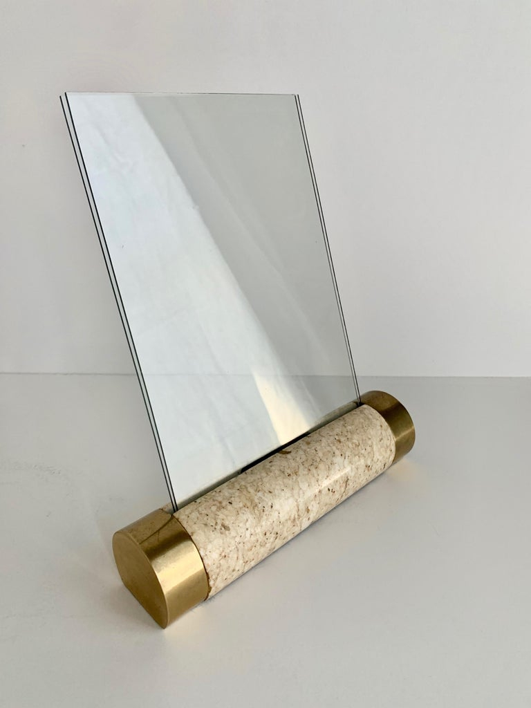 Tessellated marble solid cylinder with brass detailing on each end, the cylinder holds a two pieces of glass that together hold a photo in the format of 5 x 7. A wonderfully modern photo frame in the manner of Maitland Smith with midcentury style