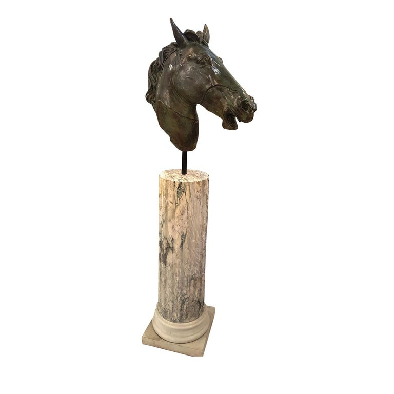 This striking decorative piece is inspired by the ancient Greek tradition of crafting bronze statues and by the ancient Roman tradition of adorning homes with busts supported with columns. The result is an elegant statue depicting the head of a