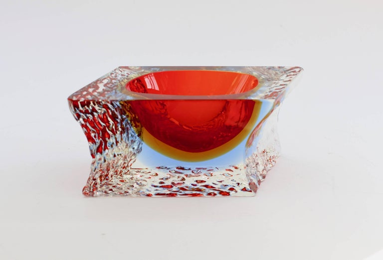 Beautiful vintage Mid-Century Italian Murano art glass bowl attributed to Mandruzzato, circa 1980s. The combination of ruby red over ochre yellow over sky blue with the textured clear 'Sommerso' ice glass looks simply stunning.