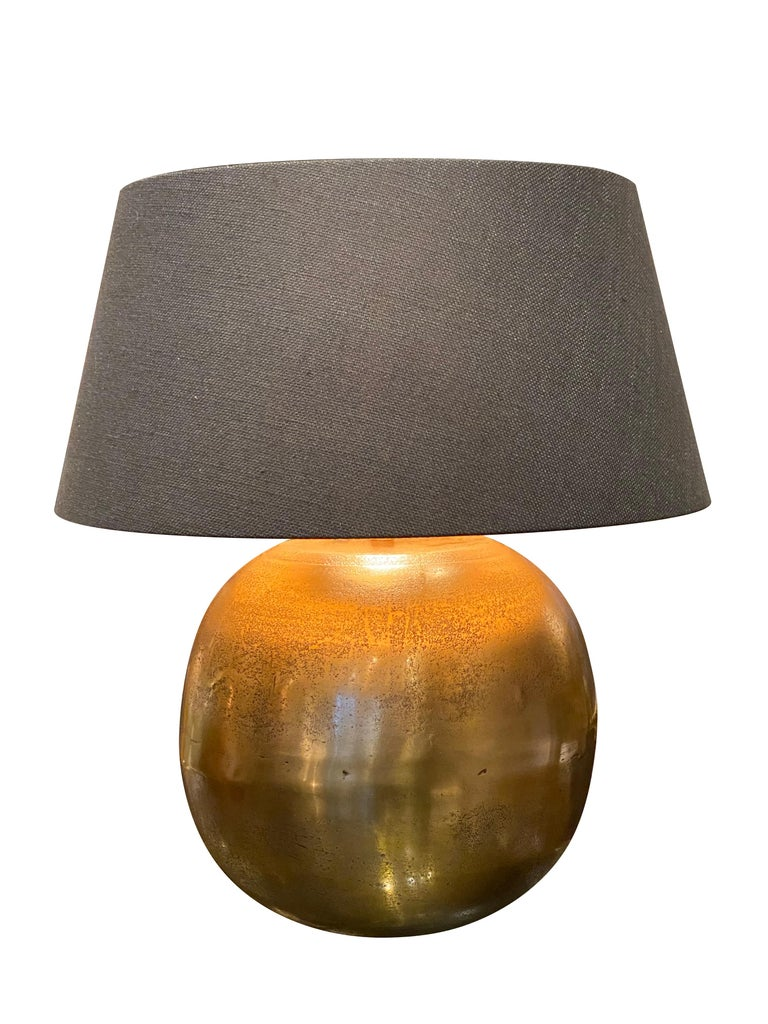 Contemporary Chinese pair of globe shaped lamps. Textured and mottled gold color made of metal. Belgian black linen shades with gold interior. Base of lamp measures 11