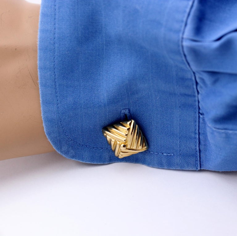 A pair of 18K yellow gold cuff links, measuring just over 1/2 an inch wide, and styled like square knots. With a ribbed design, they appear as though fabric was folded into this great design. Signed Emis, for Emis Beros of Palm Beach Florida, they