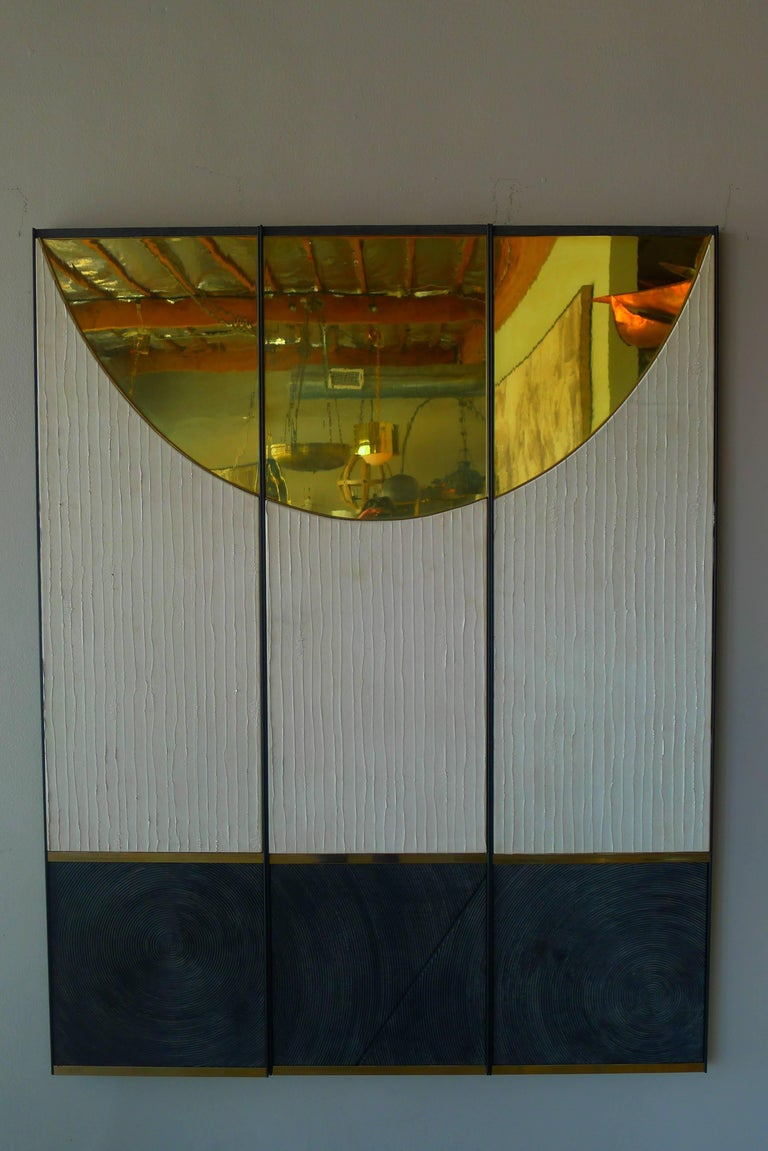 Triptych art panels by Paul Marra consisting of leather, brass, textured wood, steel frames. Shown hung as 49.5 W - each panel is 16.5 W. Brass has reflective qualities.