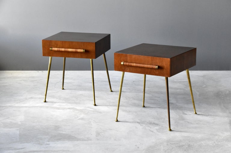 A pair of bedside cabinets / tables / nightstands / end tables designed by T.H. Robsjohn-Gibbings for Widdicomb furniture company.   Small walnut cabinets each have a drawer, grips bear original rattan, mounted on brass legs.