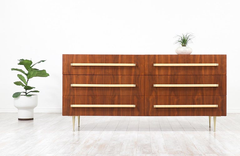 Stylish modern dresser designed by British-born architect T.H. Robsjohn-Gibbings for Widdicomb in the United States, circa 1950s. This striking design features a sturdy walnut wood case with six drawers and solid brass legs perfectly complementing
