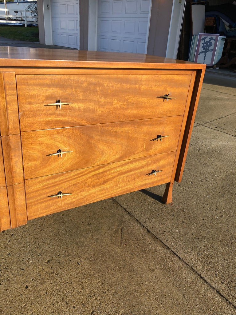 This exquisite dresser is made out of wood, solid wood, and veneer, and is in good condition. This dresser is a delightful example of the Mid-Century Modern style; it has a Classic Silhouette, charming handles, and a luscious medium walnut finish