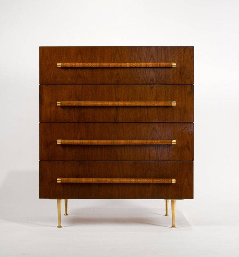 Bookmatched walnut chest of drawers with segmented oak interiors, woven cane wrapped handles, and solid polished brass hardware and feet. Signed with the Widdicomb label to the top drawers.