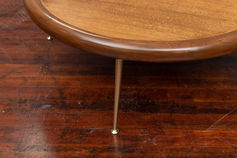 T.H. Robsjohn-Gibbings design round walnut coffee table for Widdicomb Furniture Co. Perfectly refinished in a medium walnut semigloss finish on polished brass legs and a sculptural bull nose trim, labelled.
