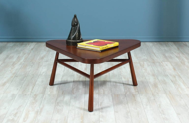 Sculptural coffee table designed by T.H. Robsjohn-Gibbings for Widdicomb in the United States circa 1950's. This versatile and beautiful Mid Century Modern coffee table features a triangular walnut wood top and three conical walnut legs connected by