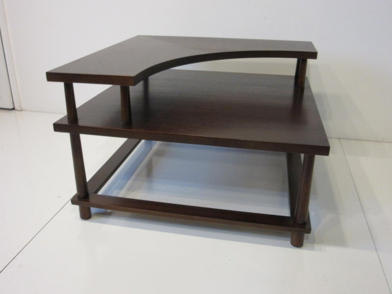 A well crafted corner / sectional table with a medium toned ebony finished having double top with upper cutout design. Sitting on reversed taped legs giving the piece a special feel, retains the original manufactures label made by the Widdicomb
