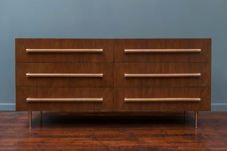 T.H. Robsjohn-Gibbings design six-drawer dresser for Widdicomb. Newly wrapped cane pulls, polished brass legs and perfectly refinished in medium walnut.