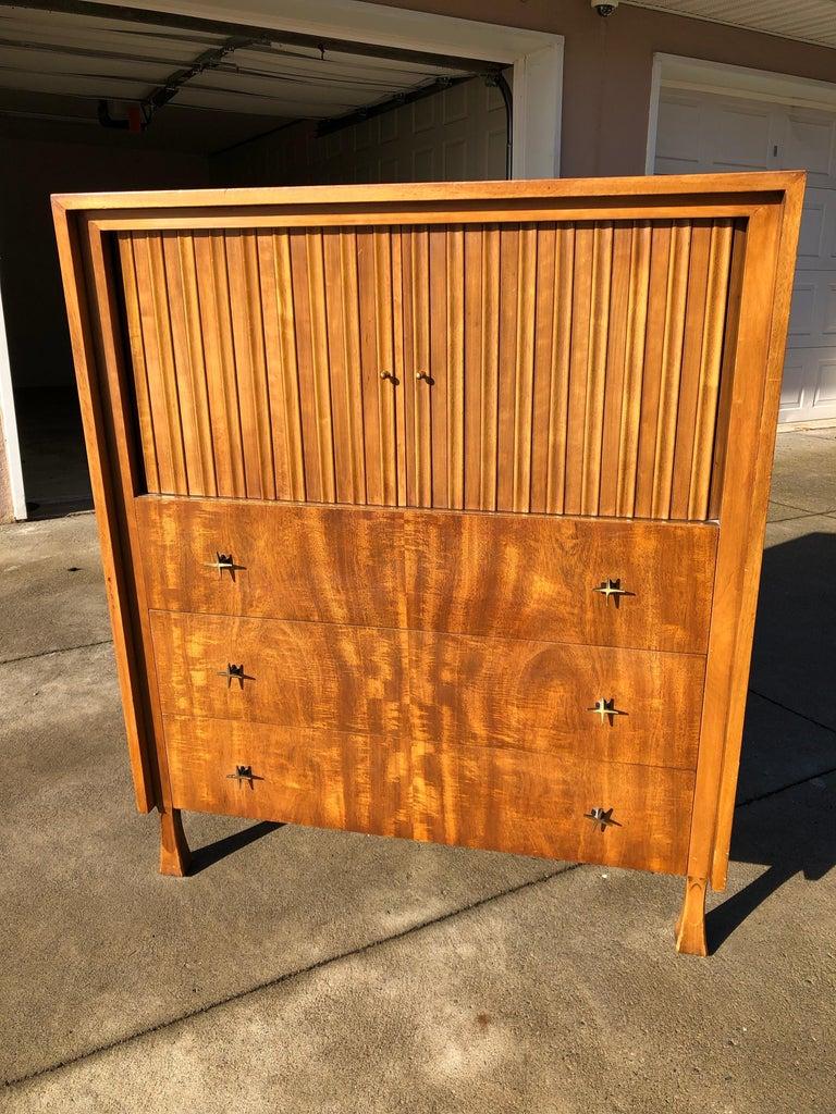 Elegant Mid-Century Modern tall dresser by John Widdicomb, with harmonica upper doors, three drawers, star like original hardware, on tapered legs. Dimensions are 40 x 20 x 48''.Original stamp inside the top drawer.