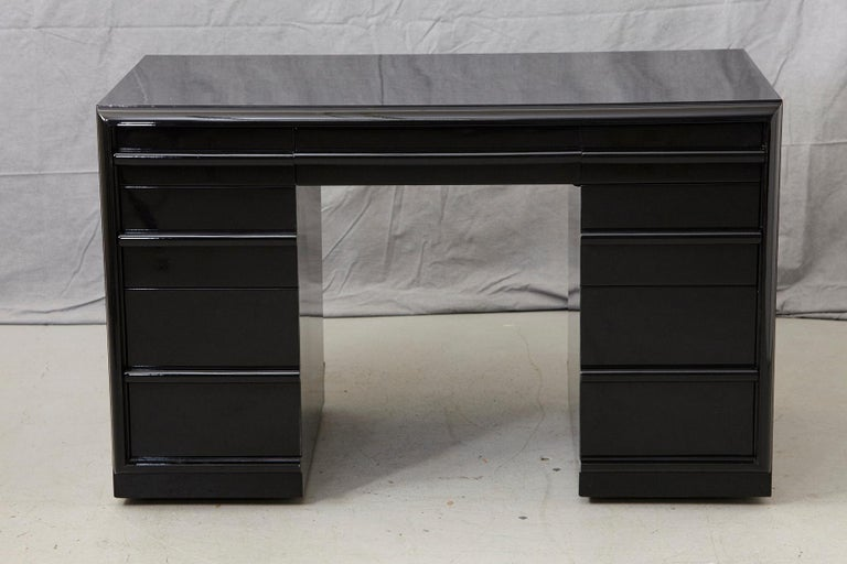 Stunning T.H. Robsjohn-Gibbings kneehole or double pedestal desk in new black piano lacquer finish. The desk is equipped with 3 drawers in each pedestal and a middle drawer mounted on casters. The kneehole measurements are as follows: W 20.25