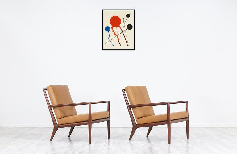Elegant modern lounge chairs designed by T.H. Robsjohn-Gibbings in collaboration with the famous Widdicomb Furniture company in the United States during the 1950s. These midcentury ergonomic lounge chairs feature a solid walnut wood frame with