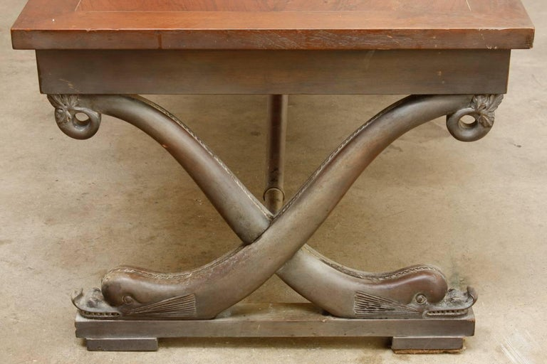 Rare T.H. Robsjohn-Gibbings (1905-1976) cocktail table for Baker furniture made in the neoclassical taste. Features an X-form curule style supports with dolphin motifs conjoined by a long stretcher. The top has a beautifully veneered four panel