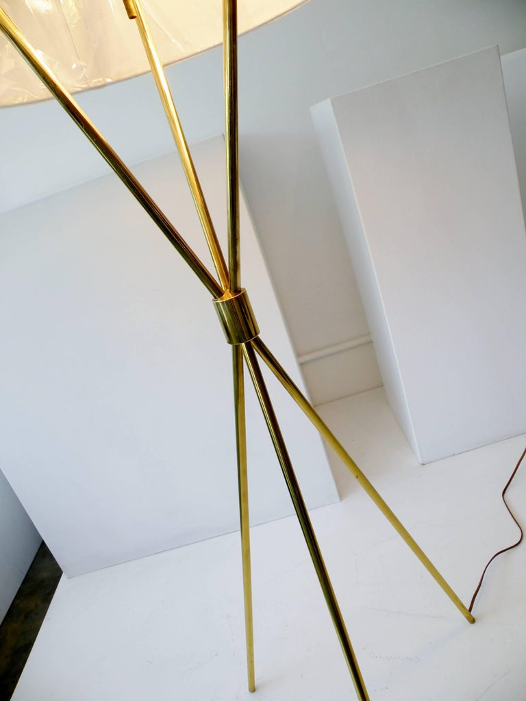 The iconic T.H. Robsjohn-Gibbings designed tripod floor or reading lamp for Paul Hansen Lighting, New York. Fine quality brass construction and marked Paul Hansen to top metal diffuser shade. Rewired with new custom-made off-white linen shade,