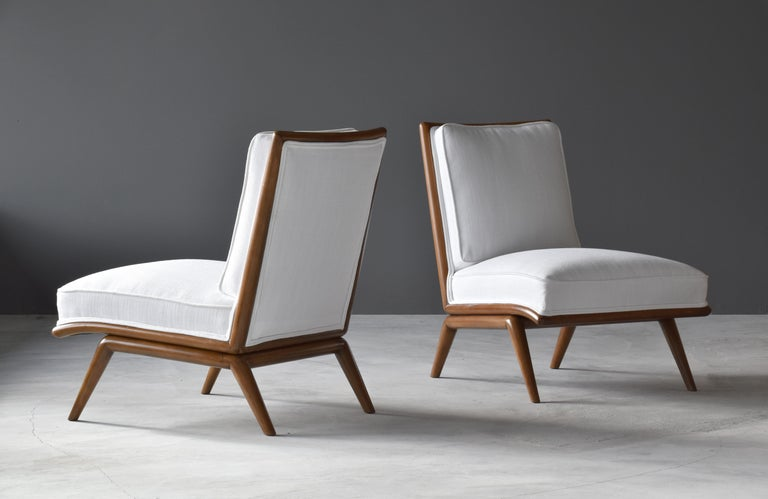 A pair of rare slipper chairs designed by T.H. Robsjohn-Gibbings. Produced by Widdicomb Furniture Company in Grand Rapids, Michigan, circa 1950s.  A mostly linear form gives this Robsjohn-Gibbings design an unusually Modern expression. The walnut