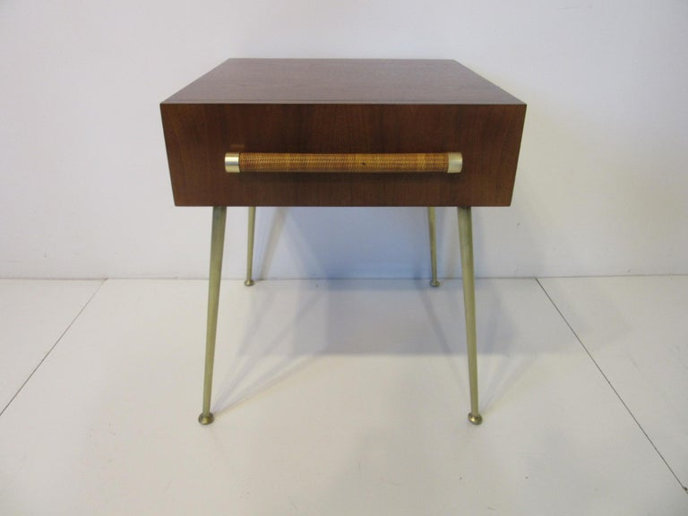 A beautifully crafted and fine quality side table / nightstand in a rich dark walnut with raffia wrapped handle and brass details to one single drawer sitting on long sexy brass legs. Retains the original fabric label in the drawer manufactured by