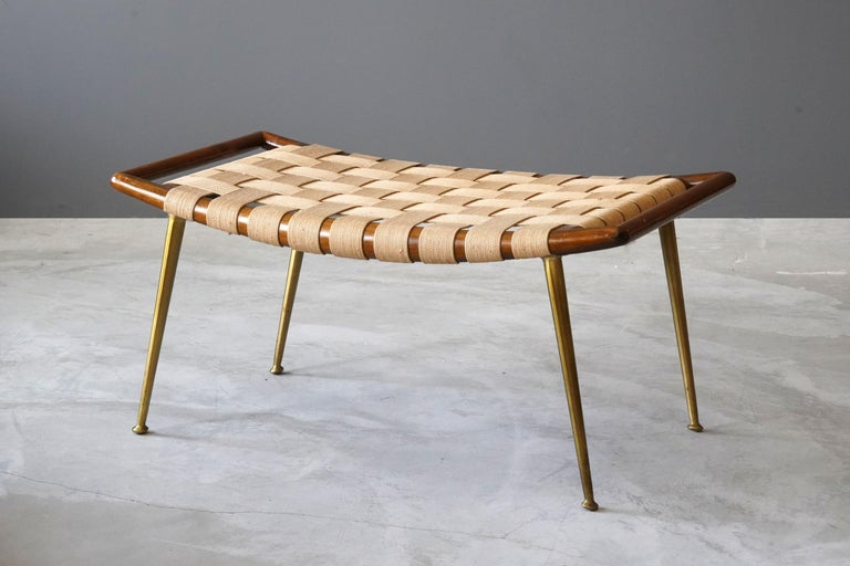 A rare small bench / stool / ottoman designed by T.H. Robsjohn-Gibbings. Produced by Widdicomb Furniture Company in Grand Rapids, Michigan, circa 1950s. Executed in brass and walnut, original webbing. Labeled.   Other American designers of the