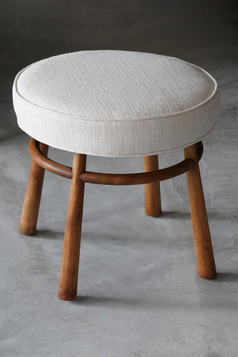 A rare stool designed by T.H. Robsjohn-Gibbings. Produced by Widdicomb Furniture Company in Grand Rapids, Michigan, circa 1950s. Executed in walnut and fabric. Labeled.   Other American designers of the period include Edward Wormley, George