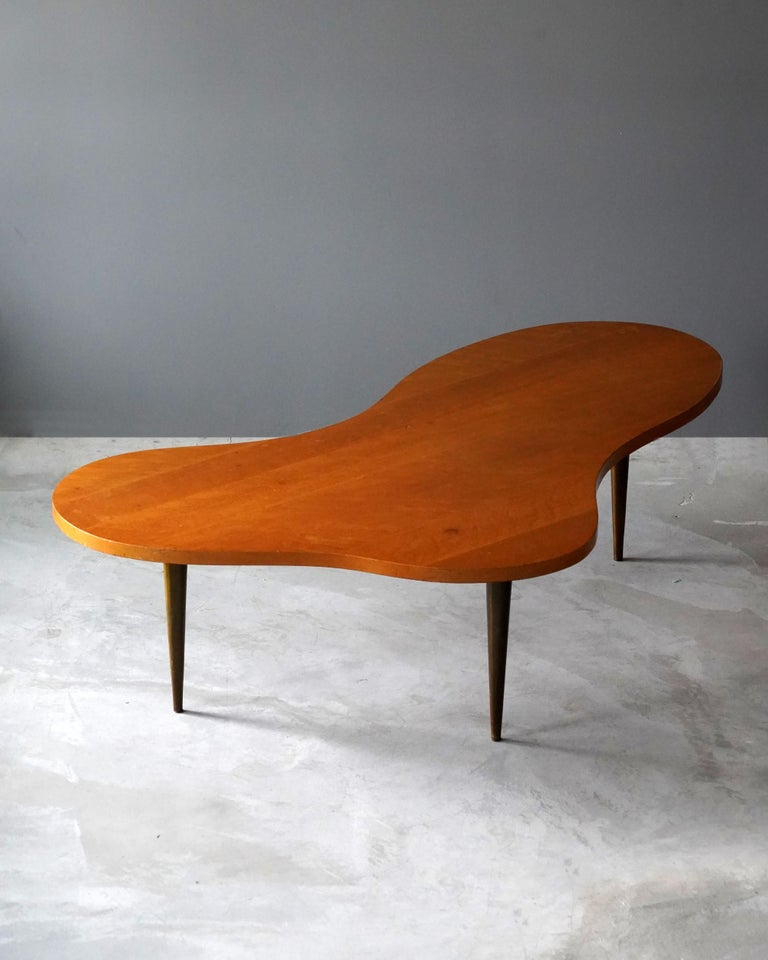 A rare large version organic coffee table / cocktail table. Designed by T.H. Robsjohn-Gibbings. Produced by Widdicomb Furniture Company in Grand Rapids, Michigan, circa 1950s. Executed in brass and walnut.   Other American designers of the period