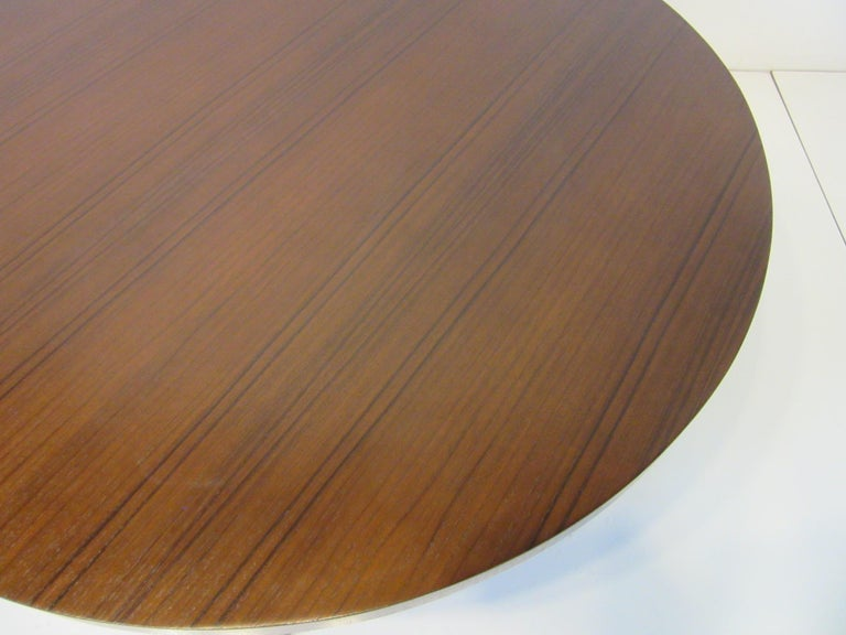 A round coffee table with dark walnut wood stretchers and legs and a beautifully grained teakwood top. Retains two manufactures labels to the bottom by the Widdicomb Furniture company designed by T.H. Robsjohn Gibbings.