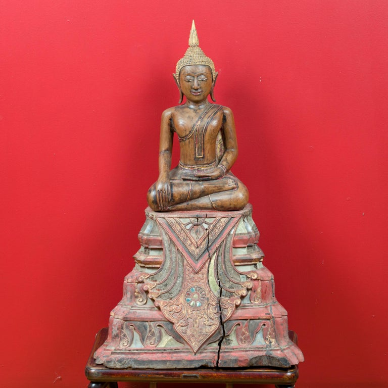 A Thai teak wood seated Buddha sculpture from the 17th-18th century, in the Calling the Earth to Witness position. Created in Thailand during the 17th or 18th century, this carved sculpture depicts the Buddha during the meditation that will bring