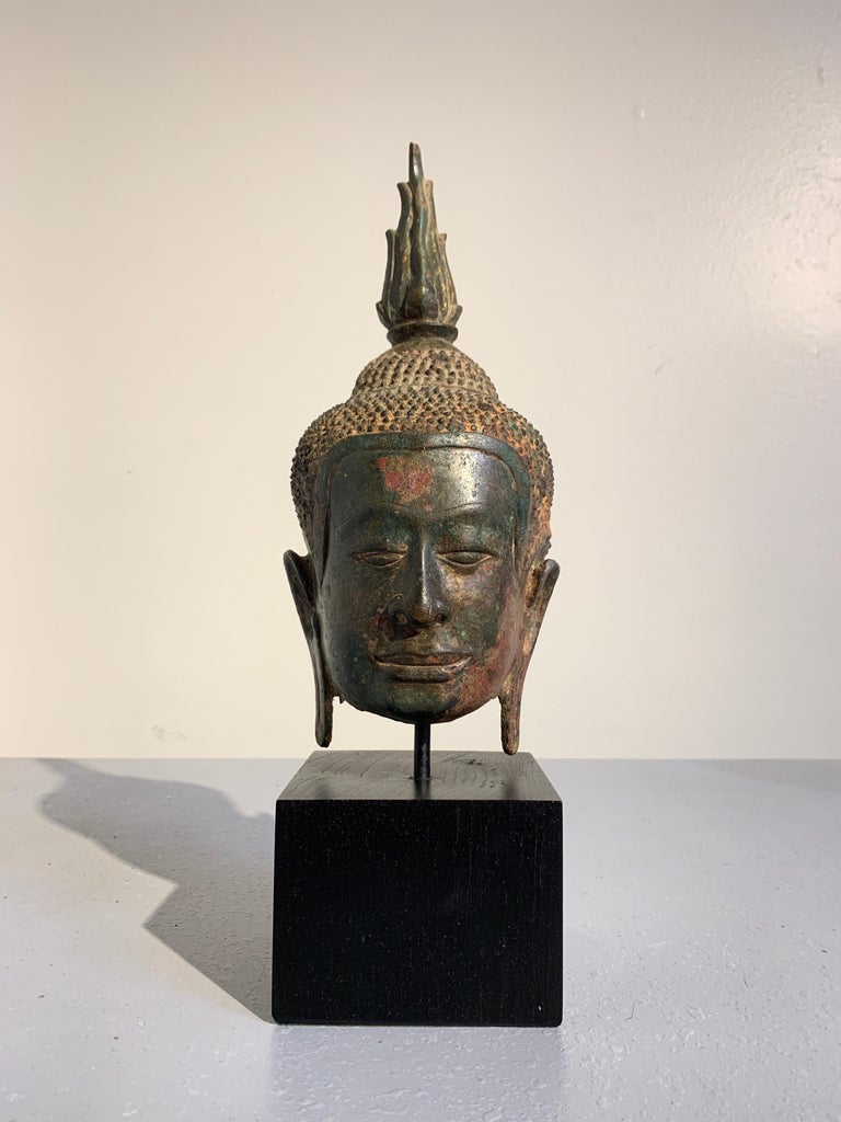 A beautifully patinated bronze Buddha head from the Kingdom of Ayutthaya, Thailand, circa 14th century.  The Buddha's face has a distinct Khmer influence, with a square face and jaw, broad nose, and long straight lips curled up ever so slightly at