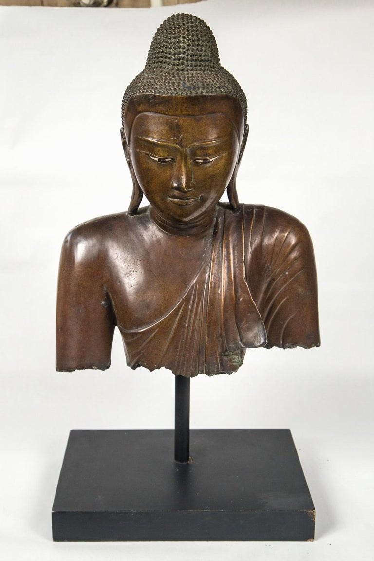 Fragment piece of the shoulders and head of this Buddha. Enameled eyes. Raised above a black base on a rod.