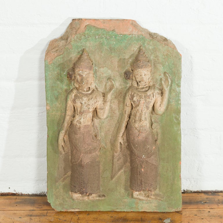 A Thai carved stone temple wall plaque depicting two ceremonial dancers with green accents. hand carved in Thailand, this antique wall plaque features a two ceremonial dancers with tall headdresses and long textured skirts, standing out beautifully