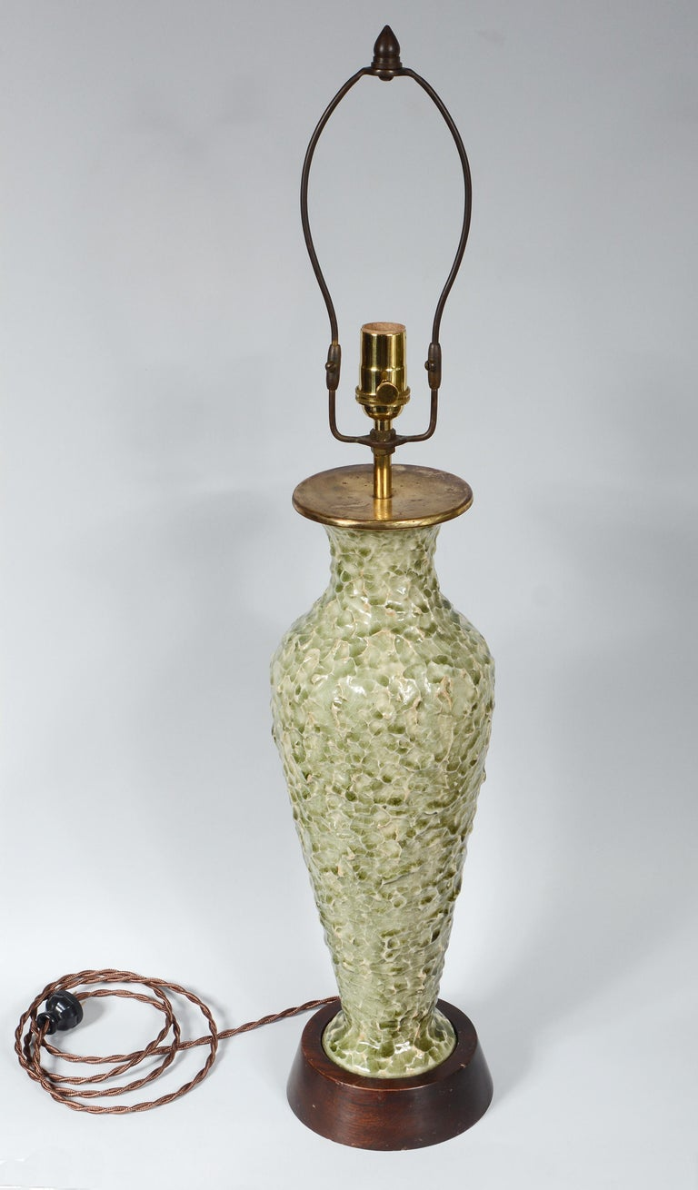 Table lamp produced by Thai Celadon in Bangkok. This lamp has an unusual textured surface. The lamp has been rewired and has a new three way socket. The base is mahogany. The lamp is 32 1/2