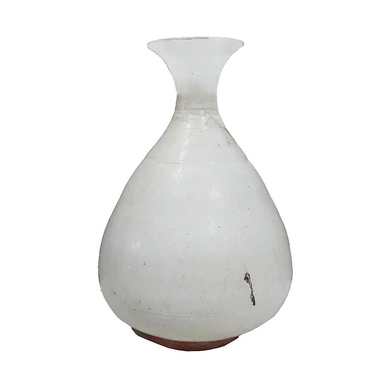 A white ceramic vase from Thailand, circa 1900. Gloss white finish, curved shape and neck, and delicate carvings throughout.