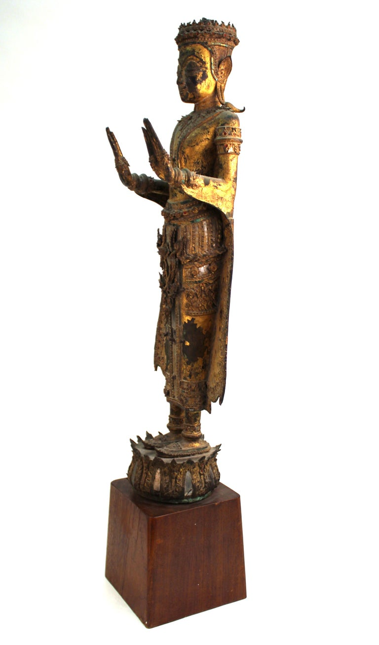 Thai antique gilded and mirrored bronze Buddha statue from the 18th century, atop a wooden base. The Buddha is wearing elaborately detailed ceremonial garments and adornments and is standing atop a lotus base. In great antique condition with