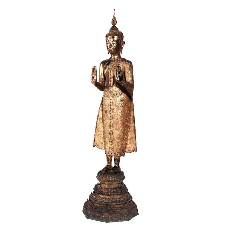 Thai gilt bronze figure of a standing Buddha, depicted upright with both hands extended forward and slightly up from the elbow, wrists bent backward, palms face forward with the long elegant fingers of the same length, reaching towards the heavens,