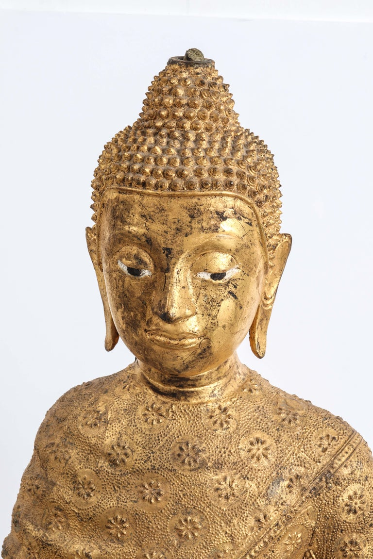 Thai gilt bronze sculpture of a standing Buddha in Abhaya mudra. The piece presents characteristics of the Rattanakosin period and dates from the 19th century/early 20th century. The figure is cloaked in a robe with all-over relief floral pattern