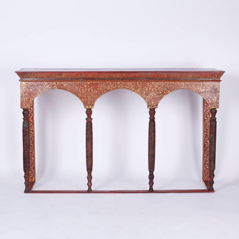 Antique Thai altar table or console with a strong architectural form. Crafted in wood with three arches supported by four turned wood columns. The table is painted in a rustic polychrome technique and aged to perfection.
