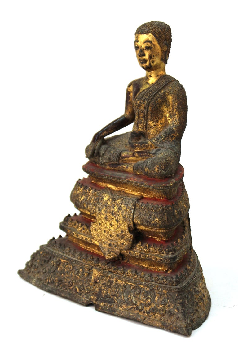 Thai Rattanakosin period cast gilt bronze Buddha from the mid-19th century, seated on a multi-tiered throne base. The backside of the statue has rings to be used as attachments to secure it to a wall within a temple setting. The statue is in great