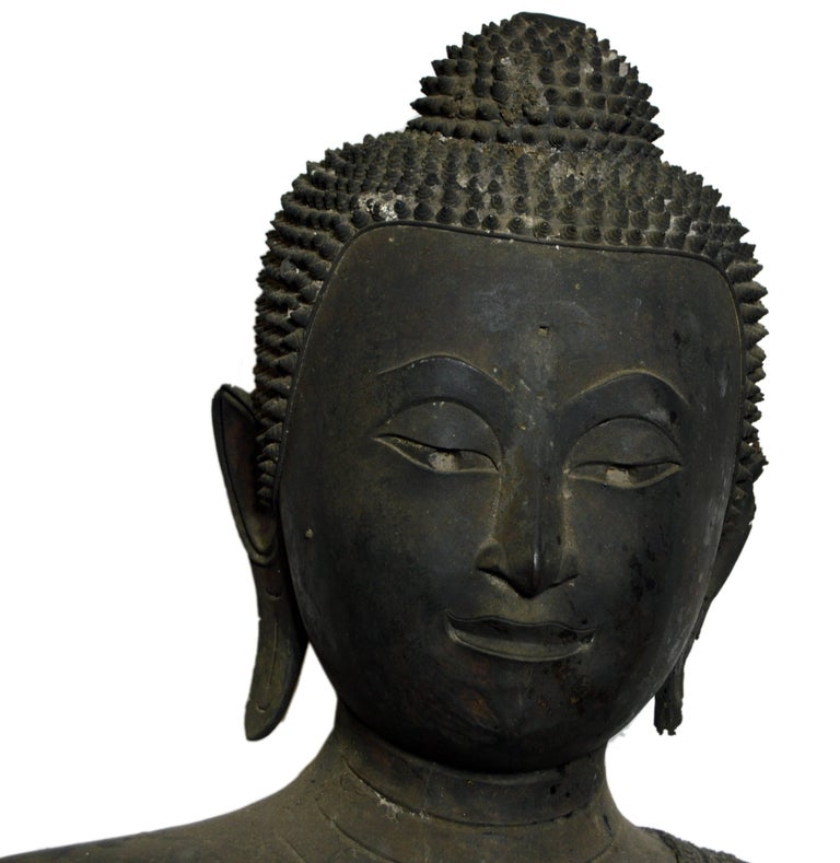 A turn of the century (19th to 20th) bronze Thai seated meditative Buddha statue with a dark patina. This Thai statue displays a seated Buddha that seems to share some similarities to the style of Buddha common in the Pala Empire in northern India