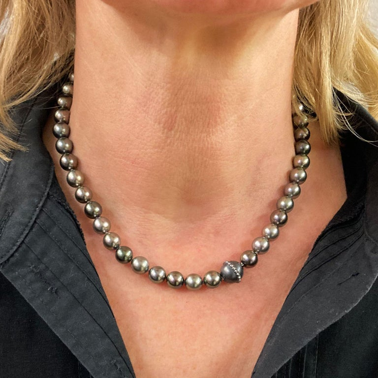 This Thaiti-Pearl-Choker Necklace shines in different grey colors.The pearls have a perfect luster. The clasp in 18 kt white gold is finished with black rhodium and decorated with 36 Brillants with a total weight of 0.16 ct G vvs pave setted. Total