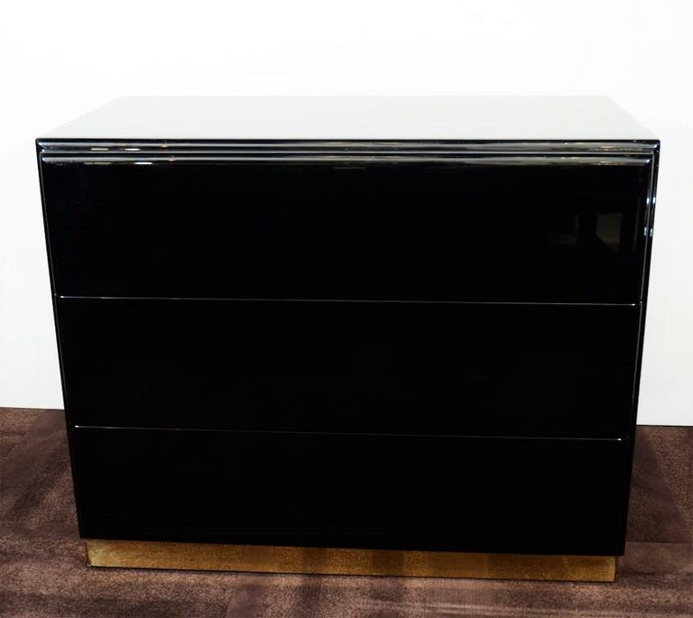 Amazing pair of large nightstands or chests by Thayer Coggin. Freshly lacquered in black. Each chest is fitted with three spacious wood drawers on a brass plinth base.