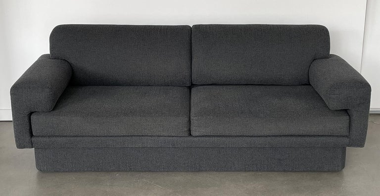 Modern fully upholstered sofas by Thayer Coggin, circa mid-1980s. ONE AVAILABLE. Priced individually. Reupholstery required. These sofas feature a fully upholstered frame with plinth base, modern arm that wraps around the seat cushion, two loose