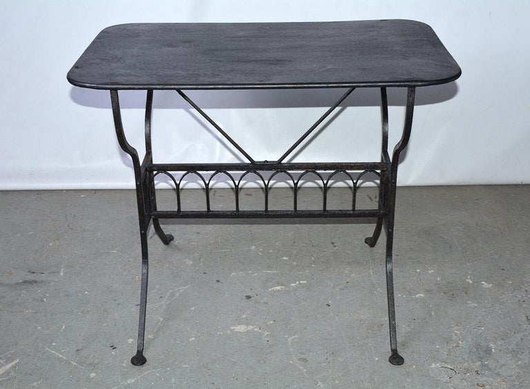The 19th century French iron garden table is painted black and has a row of faux gothic arches embellishing the stretcher that secures splayed legs. The top is also made of iron. Most certainly sturdy enough for potted plants, porch use and also the