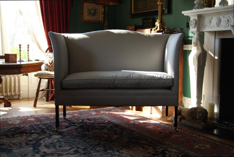 The Admiral sofa by Noble and Thane - adapted from an elegant English wingback design.   Shown here in full rigging, with optional brass castors and bolster cushions, finished in a vintage style navy and white striped ticking.  Both the frame making