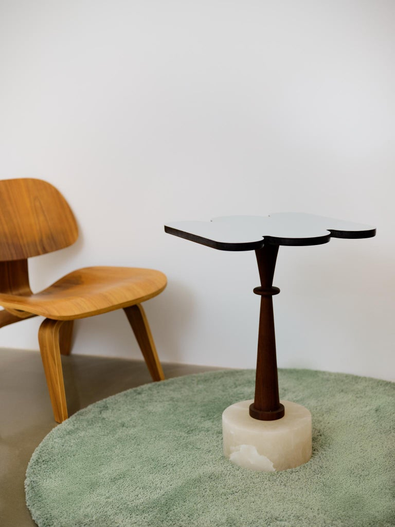 Contemporary side table made mixing stone wood and metal following the Art Deco fashion of conceiving a piece. A solid yet traslucent cylindric white Alabaster base stems a chess piece shaped column that holds the aluminum top cloud shaped. Unique