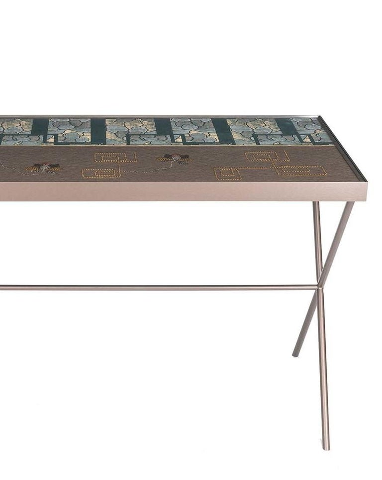 The complex decoration that graces this desk will stand out in a modern or eclectic interior, where it will add a unique and warm elegance to a study or living room. The metal structure has a sophisticated honey-brown varnish that gives it a