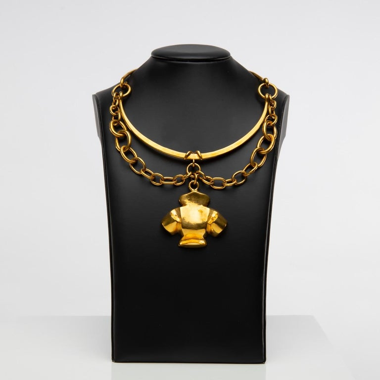 Necklace made up of two rigid parts surrounding the neck.    The front part is decorated with large links, in its centre, a