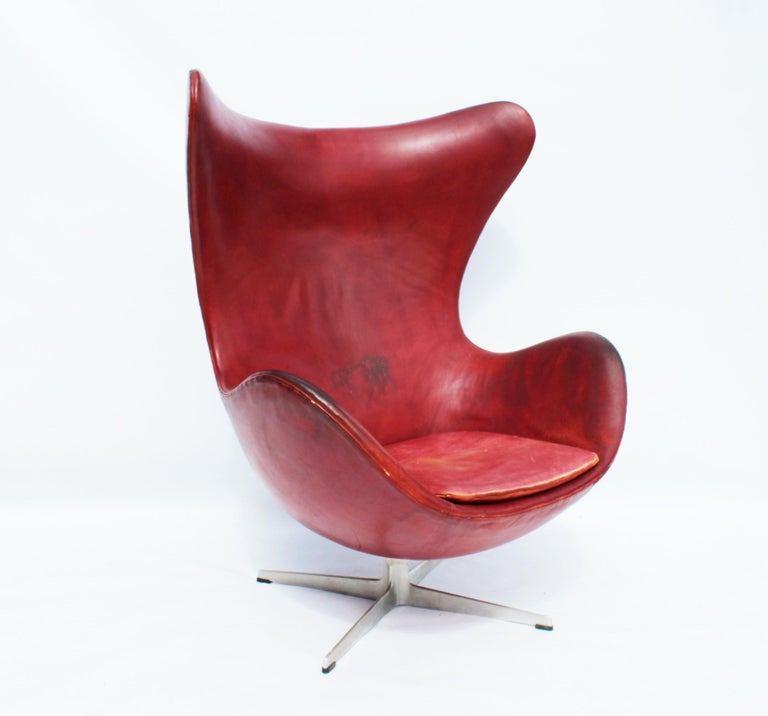 The egg, model 3316, designed by Arne Jacobsen in 1958 and manufactured by Fritz Hansen in 1963. The chair is with original patinated upholstery with red elegance leather and is in great vintage condition. The egg is with the swivel function.
