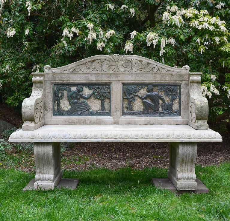 A garden seat, the carved stone camel-form back with scrolled crest above inset bronze panels in the Art Deco style, the panels representing the Fall season, with one panel depicting a female figure picking apples and another depicting a male figure
