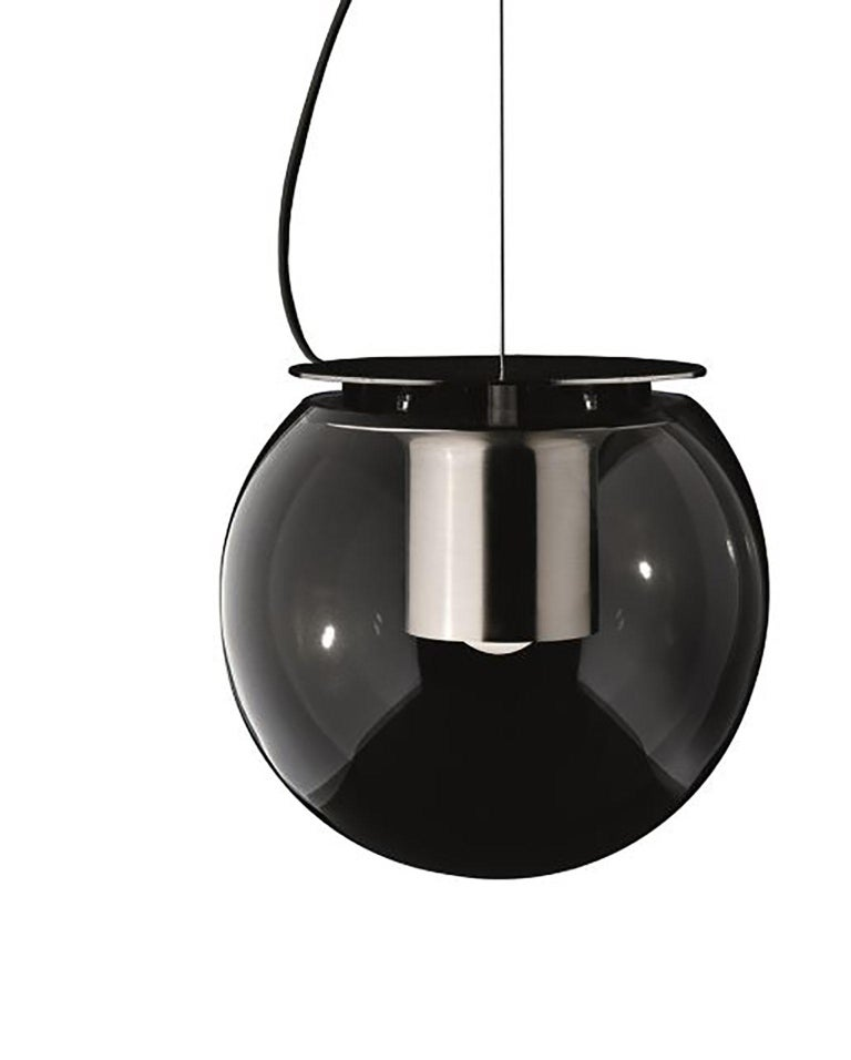 Globe suspension lamp designed by Joe Colombo for Oluce. This lamp is a spherical blown glass body with a cylindrical nickel reflector. The suspension cable of the lamp can be adjusted up to 3m so that it can be best suited for any area. The