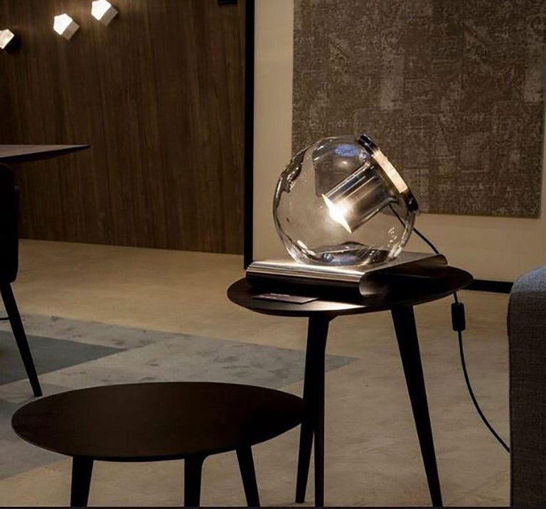 The Globe table lamp designed by Joe Colombo for Oluce. It is a simplistic and appealing design manufactured from hand-blown glass, producing a remarkable ambient light with the help of an internal metal reflector. The twisted metal reflector (as